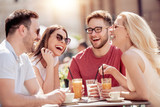 Four laughing friends enjoying coffee in a cafe - 211957315