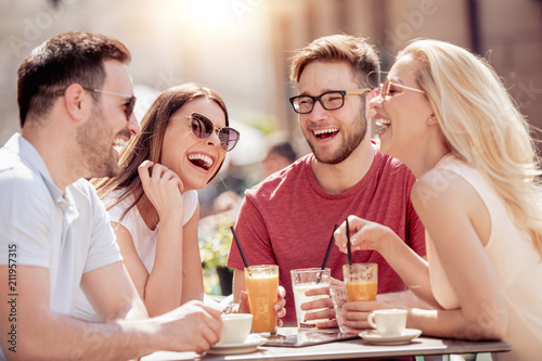 Poster Four laughing friends enjoying coffee in a cafe