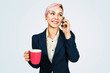 Young business woman holds cup of coffee and speaks on a smartphone, isolated on blue background