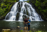 Travel New Zealand. Young tourist couple/friends overlooking waterfall. Popular tourist attraction in North Island. Long exposure falling water. Summer holidays. Natural, outdoor, travel background.