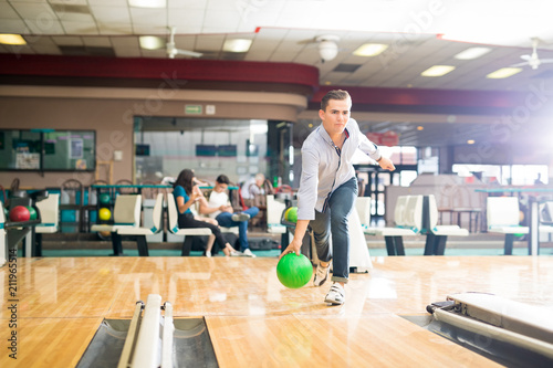 Leinwanddruck Bild Dedicated Teen Playing Bowling With Green Ball In Club