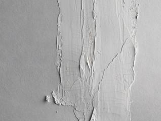 Grey brush stroke on gray empty wall.
