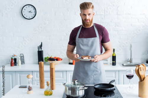 handsome bearded young man in apron holding delicious beef steak on plate and looking at camera - 211969732