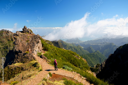 Woman alone looking at valley and mountains in sunny weather, Ninho da Manta, Pico do Areeiro, Madeira island, Portugal - 211972133