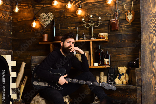 Man bearded musician enjoy evening with bass guitar, wooden background. Guy in cozy warm atmosphere play relaxing soul music. Favourite activity. Man with beard holds black electric guitar - 211976782