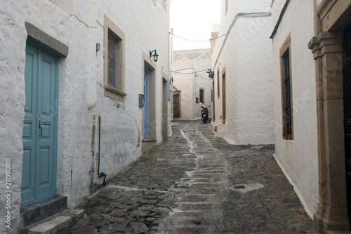 A view of a narrow street with arch and wooden windows and doors with white wall stone architecture of the island Patmos, Greece  - 211980180