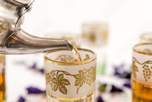 Fototapeta The Time of Tea Break. Flat lay of someone throwing tea in a cup with a teapot on white table background.