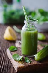 Grüner Smoothie mit Spinat und Gurke auf rustikalem Untergrund