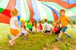 Leinwanddruck Bild - Cheerful kids hiding under rainbow canopy