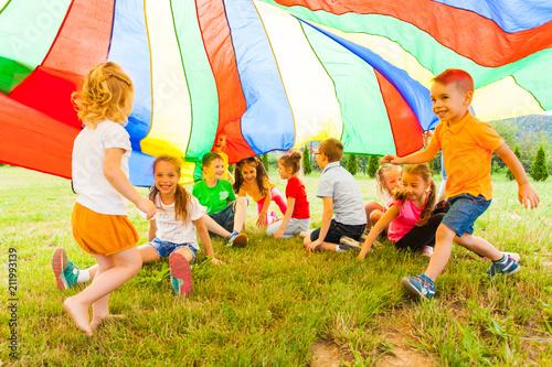 Leinwanddruck Bild Cheerful kids hiding under rainbow canopy