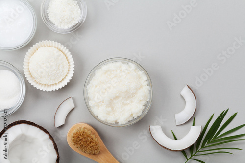 Body scrub of coconut oil, sugar and shavings in glass jar top view. Homemade organic cosmetic for peeling and spa care. Flat lay. - 212025501