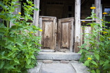 The carved porch of a wooden old traditional house in Poland. Yellow flowers grow near the house   - 212040527