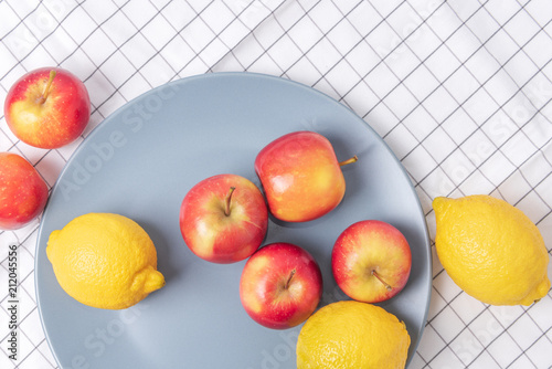 Fresh apples and lemons in a plate on checked table napkin. - 212045556