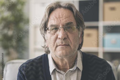 Foto Murales Old man sitting on sofa and looking at camera