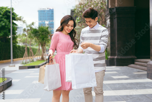 Fototapeta Portrait of happy couple with shopping bags after shopping in city