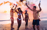 Group of friends having fun running on the beach with smoke bombs