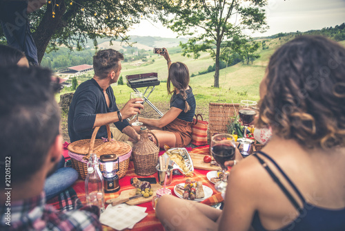 Group of friends spending time making a picnic and a barbeque - 212051122