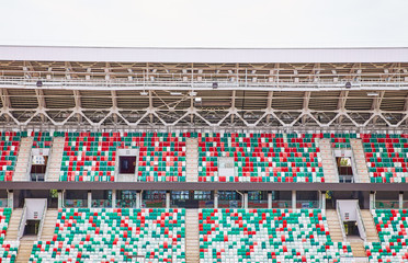 Empty stands of a modern stadium without spectators and colored chairs in the center of the arena