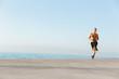 Leinwanddruck Bild - Mature sportsman running on the beach outdoors.