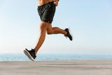Sportsman running on the beach outdoors. - 212058523