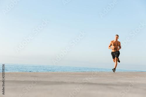 Leinwanddruck Bild Mature sportsman running on the beach outdoors.