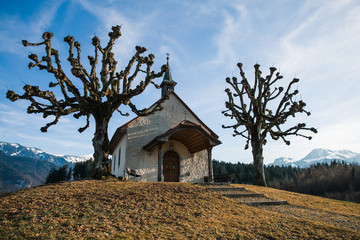 Small Swiss Chapel in Winter with Mountains in the Background © Angelina