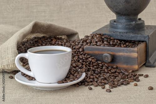 Fotobehang Koffiebonen taza de cafe con un saco de granos y un molinillo antiguo sobre arpillera