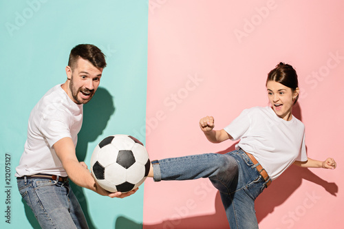 The young football fans plaing with ball on blue and pink trendy colors.