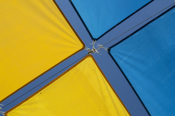 fondo con lona de dos colores/Toldos decorativos de dos colores amarillo y azul formando una x en verano en una calle de Madrid. España