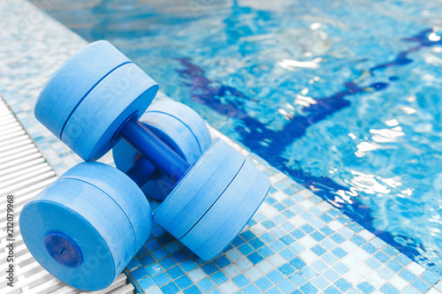 Leinwanddruck Bild dumbbells equipment for aqua aerobics sport near swimming pool