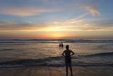 Famille sur la plage au coucher du soleil