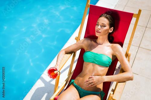 Leinwanddruck Bild Woman enjoying cocktail at pool