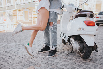 Gril is jumping near guy. Her legs are in air. They are standing beside motorcycle in the middle of street. They have a date today.