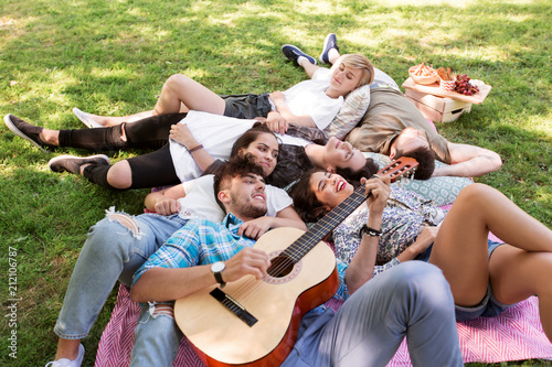 friendship, leisure and summer concept - group of happy smiling friends with guitar chilling on picnic blanket - 212106787