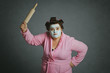 Leinwanddruck Bild - femme ronde et drôle avec bigoudis frappant avec un rouleau à pâtisserie