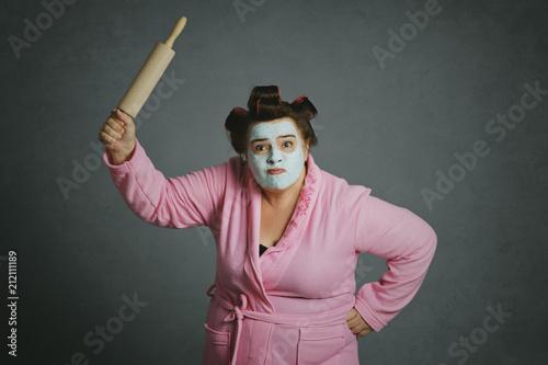 Leinwanddruck Bild femme ronde et drôle avec bigoudis frappant avec un rouleau à pâtisserie