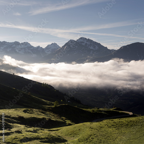 Fototapeta mountainscape near col de vars in french provence alps on early summer morning with clouds raising in valley and blue sky