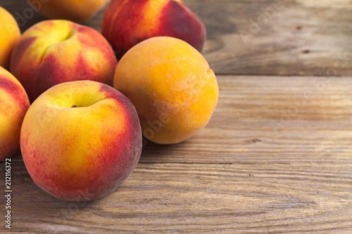A group of ripe peaches on wooden surface - 212116372