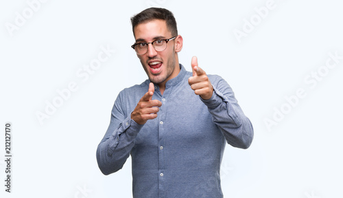 Handsome young elegant man wearing glasses pointing fingers to camera with happy and funny face. Good energy and vibes.