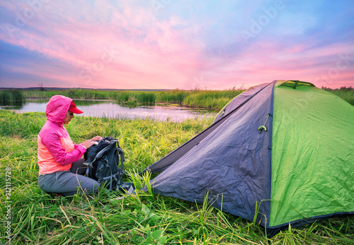 Fotobehang Pistache Girl in pink jacket opens her backpack near tent on the river ba