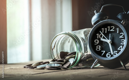 Coins with alarm clock - money savings concept.