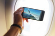 Man takes pictures on his smartphone aerial view of the small city, ground and clouds from the aircraft during the flight.  - 212141581