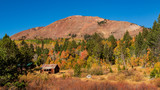 Cabin at foot of hill with autumn colored trees - 212145534