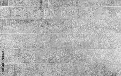 Fototapeta Full frame background of an old and aged wall made of stone blocks in black and white