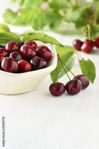 Aluminium Kersen organic cherries, , freshly picked organic cherry in a bowl on a white wooden table, vertical with a blurred background to ad copy space