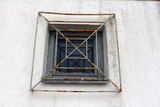 Wooden frame rectangle window with partially rusted metal bars mounted on wall outside - 212148908
