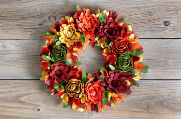 Colorful Wreath made of wooden flowers and leaves on vintage wood background