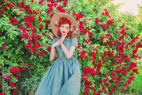 Leinwanddruck Bild Valentines Day background. Young retro girl with red lips in stylish mint dress in beautiful summer roses garden. Valentines Day beauty redhead model with hairstyle on background of bush of roses.