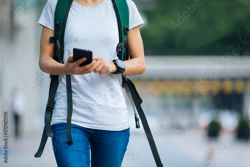 Fototapeta young woman walking with smart phone in modern city