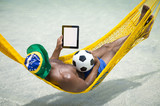 Brazilian footballer wearing flag hat and using tablet computer with a soccer ball relaxing in bright sunlit hammock on beach over the sea. - 212166329